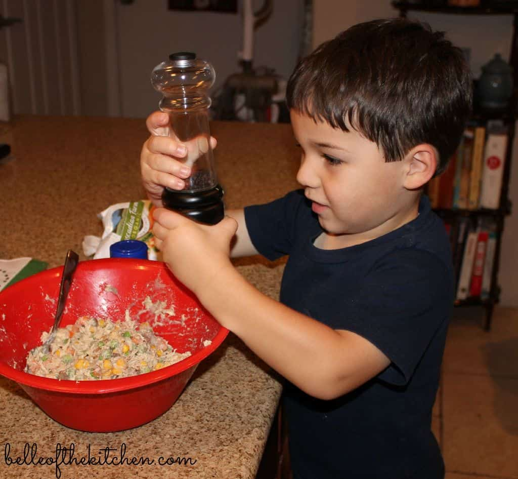 A little boy that is holding a pepper grinder over a bowl of food