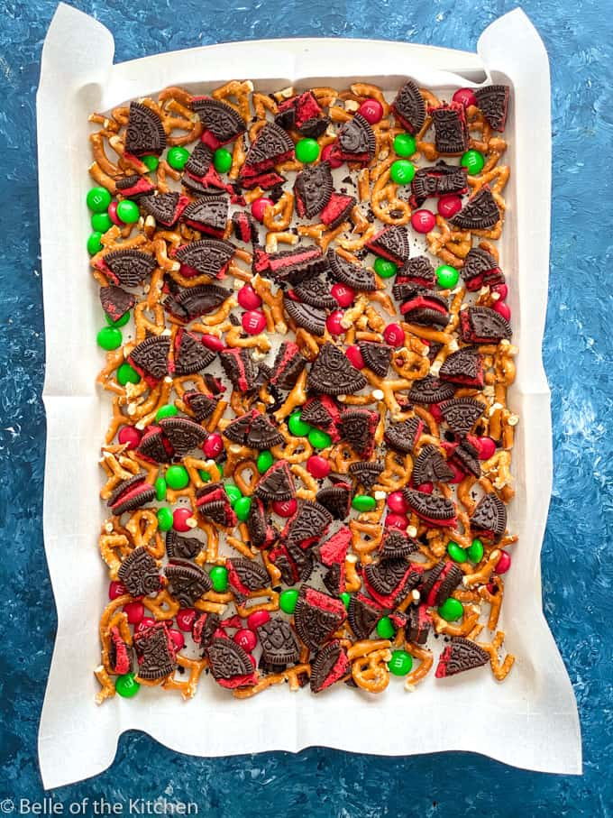 blue background with a sheet pan covered in white paper, full of M&Ms, Oreos, and pretzels
