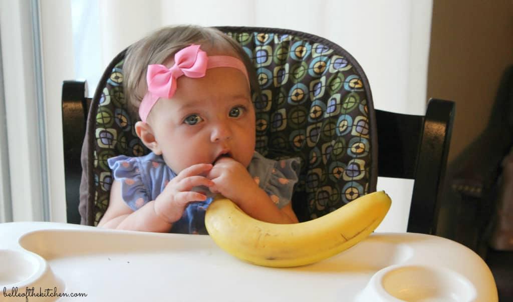 A little girl holding a banana