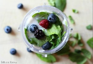 A cup filled with berries and spinach