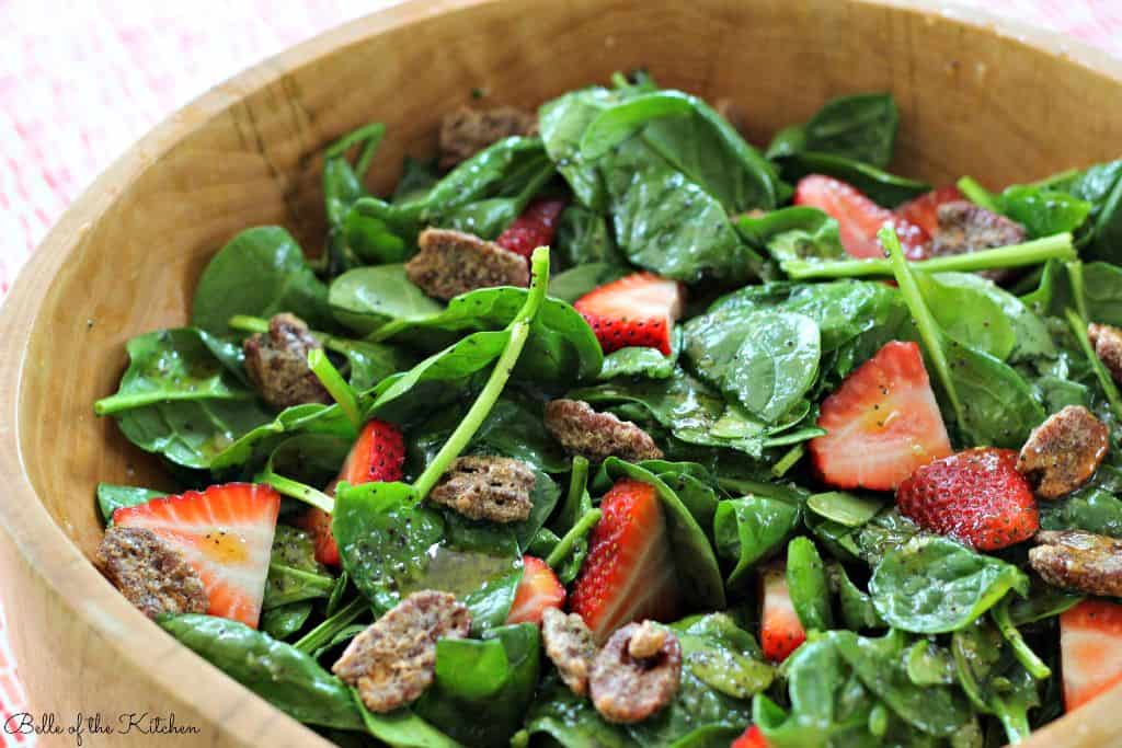 A bowl of salad, with strawberries and pecans