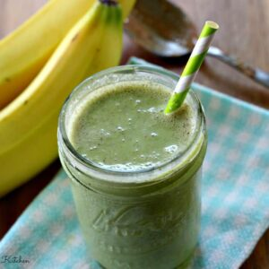a green smoothie in a jar with a straw