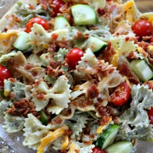A close up of a bowl of pasta salad topped with cucumber, bacon, tomatoes, and shredded cheese