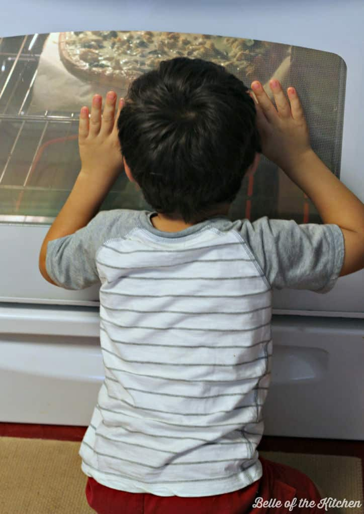 A little boy looking in the oven