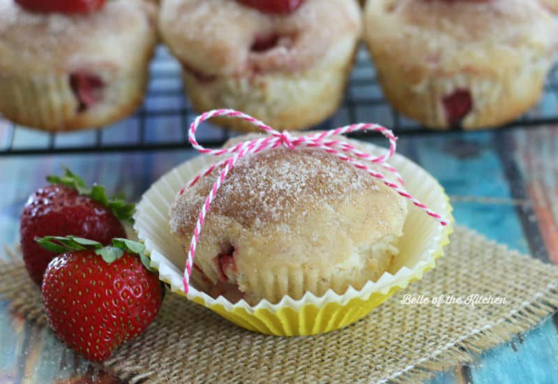 a muffin with strawberries beside it, wrapped in string