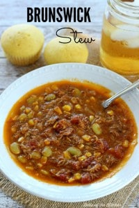A white bowl full of Brunswick stew next to cornbread and a glass of sweet tea