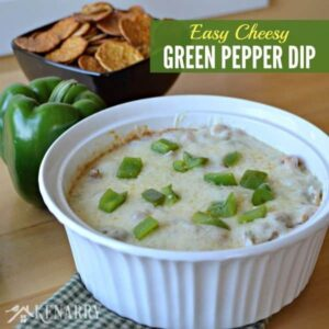 A bowl of green pepper dip on a table with a bowl of chips beside it