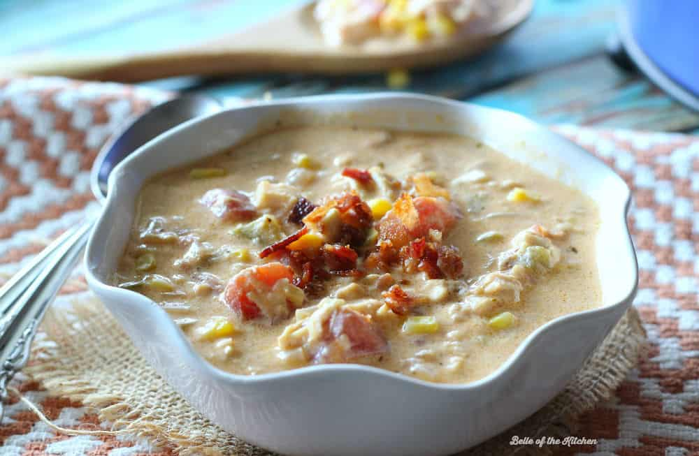 A white bowl full of soup topped with bacon