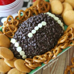 A cheeseball shaped like a football topped with chocolate chips and surrounded by pretzels and vanilla wafers