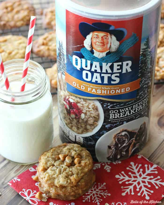 A close up of a stack of oatmeal cookies next to a glass of milk and a package of oatmeal