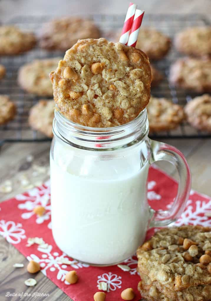 A glass of milk with an oatmeal cookie on top