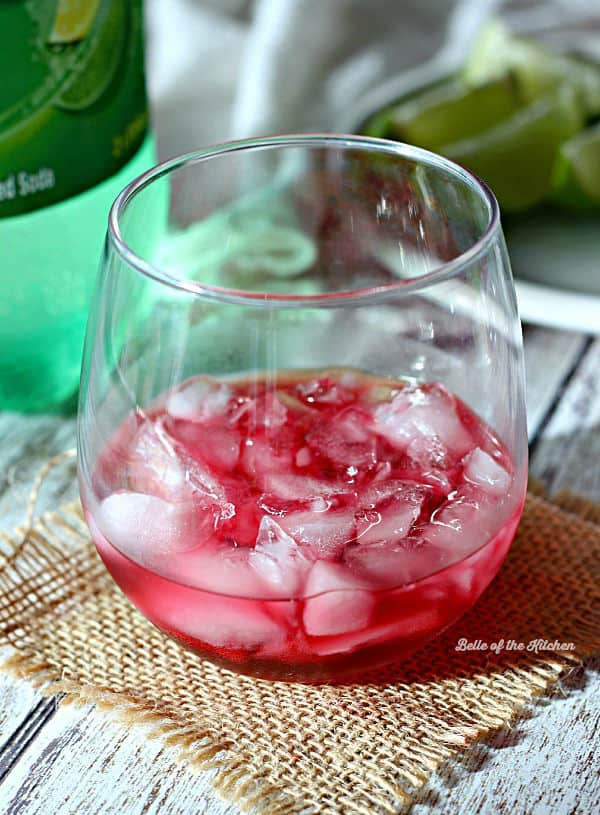 A close up of a wine glass with limeade and ice