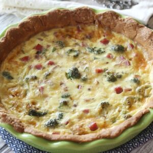 a green pie plate filled with broccoli quiche