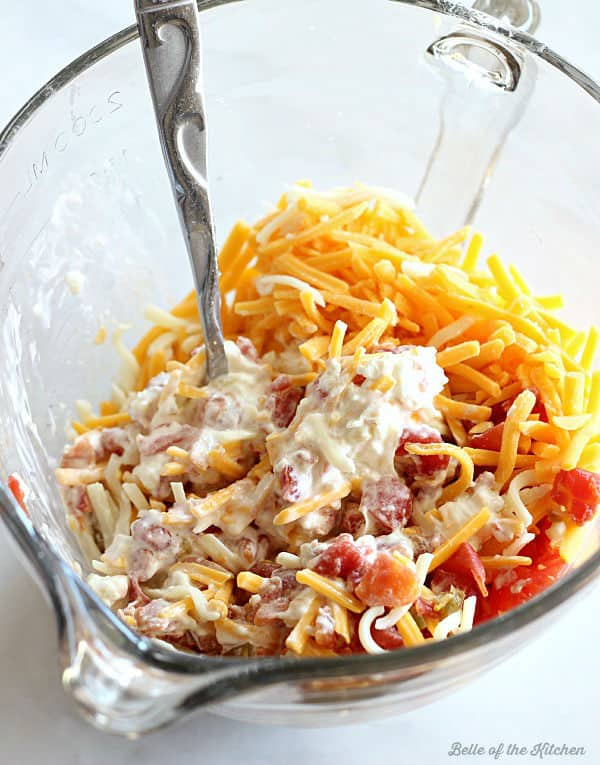 A bowl of cheese, mayonnaise, and tomatoes