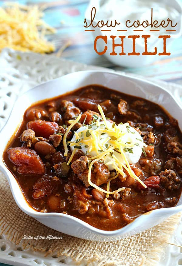 A bowl of chili topped with sour cream and shredded cheese