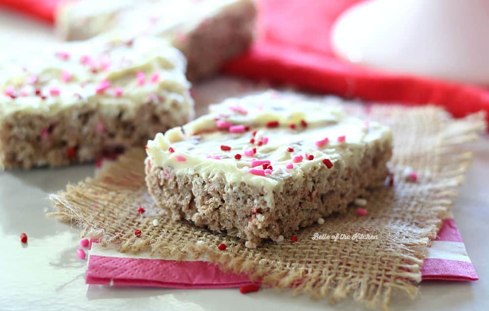 A close up of a Rice Krispie treat topped with frosting and pink sprinkles