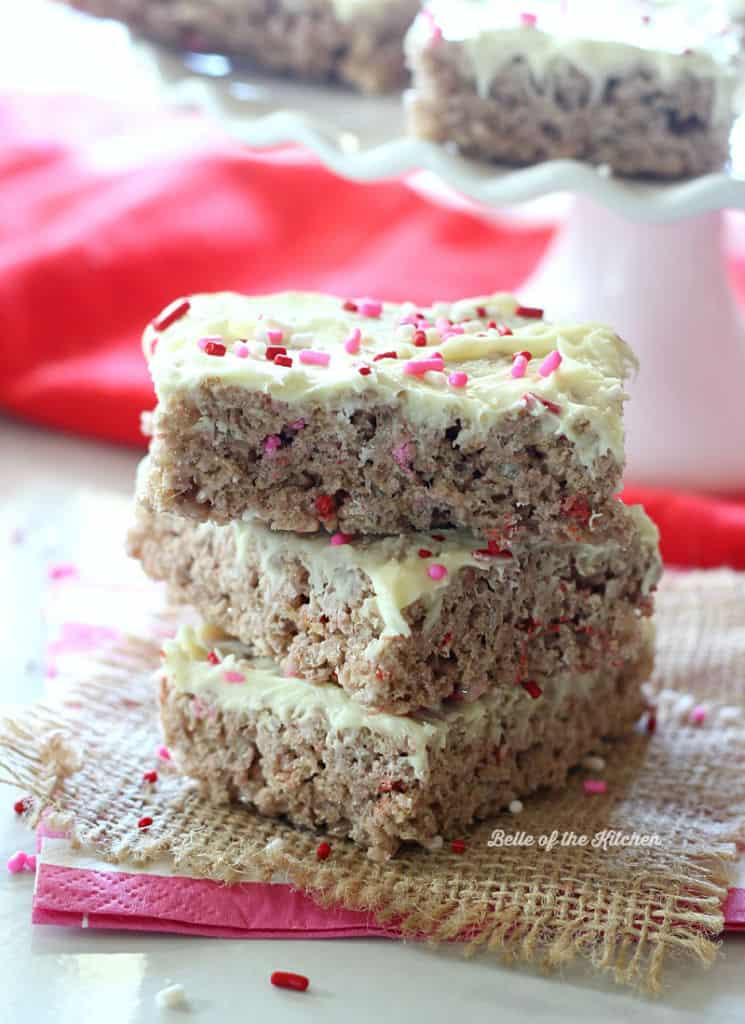 a stack of Rice Krispie treats topped with frosting and pink sprinkles