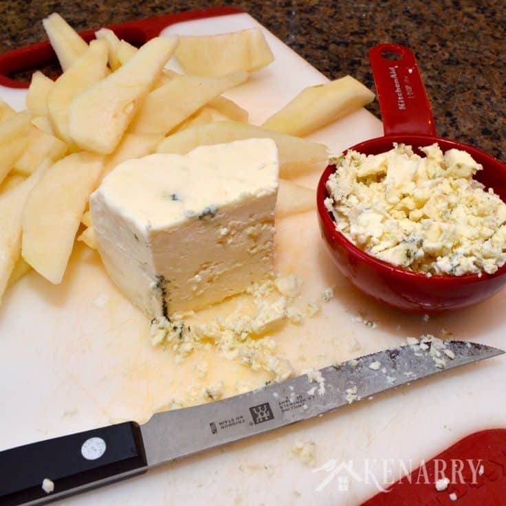 a cutting board with sliced pears, cheese, and a knife