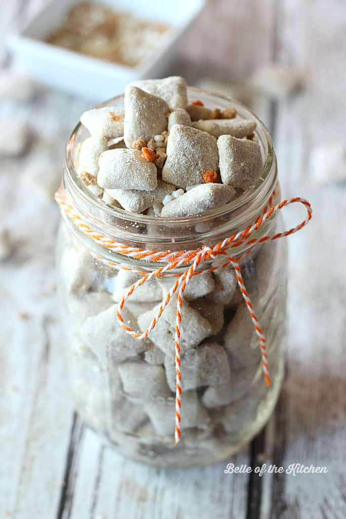 A close up of a mason jar of carrot cake puppy chow topped with orange and white sprinkles
