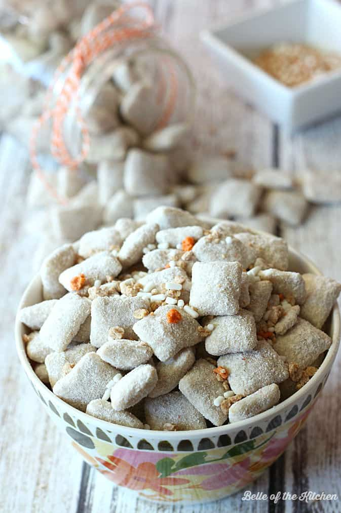 A close up of a bowl of carrot cake puppy chow topped with orange and white sprinkles