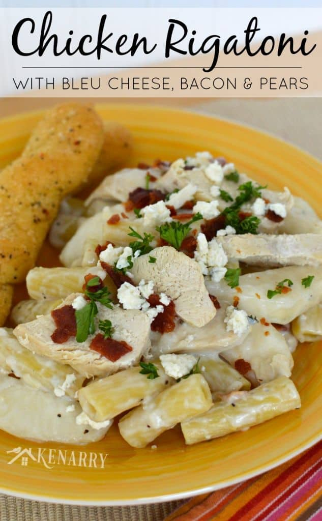 A plate of pasta with chicken and bread sticks on the side