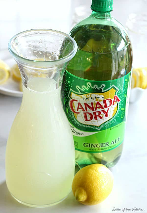 a carafe full of lemonade next to a bottle of ginger ale