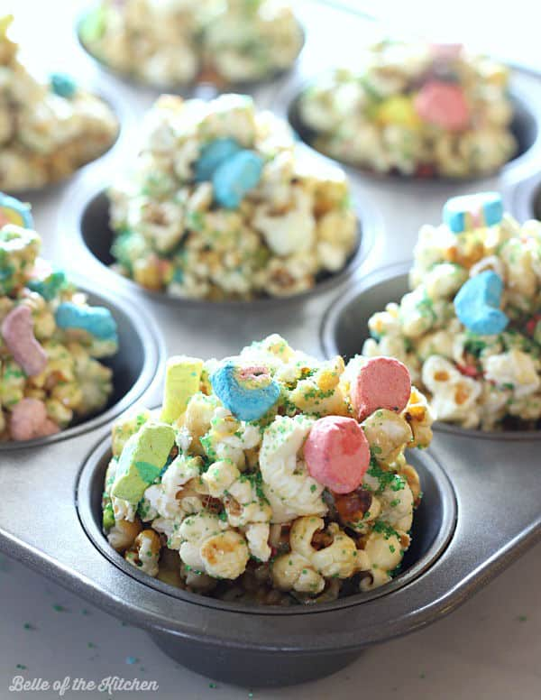popcorn balls in muffin cups topped with lucky charms marshmallows