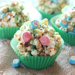 popcorn balls in green paper muffin cups topped with lucky charms marshmallows