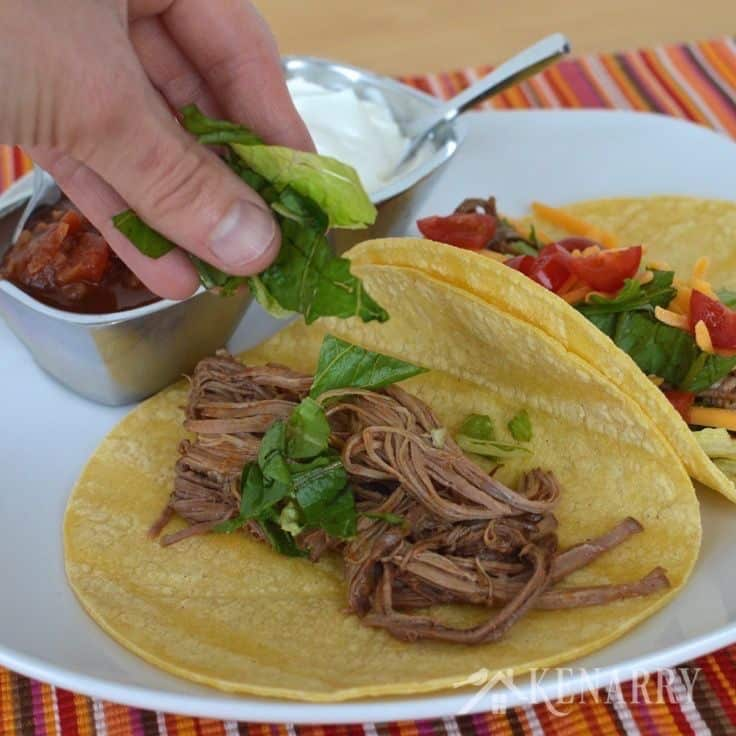 shredded beef on a taco shell on a plate topped with lettuce