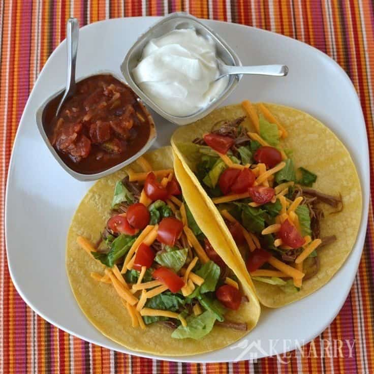 two tacos on a plate with shredded beef on a taco shell beside bowls of salsa and sour cream