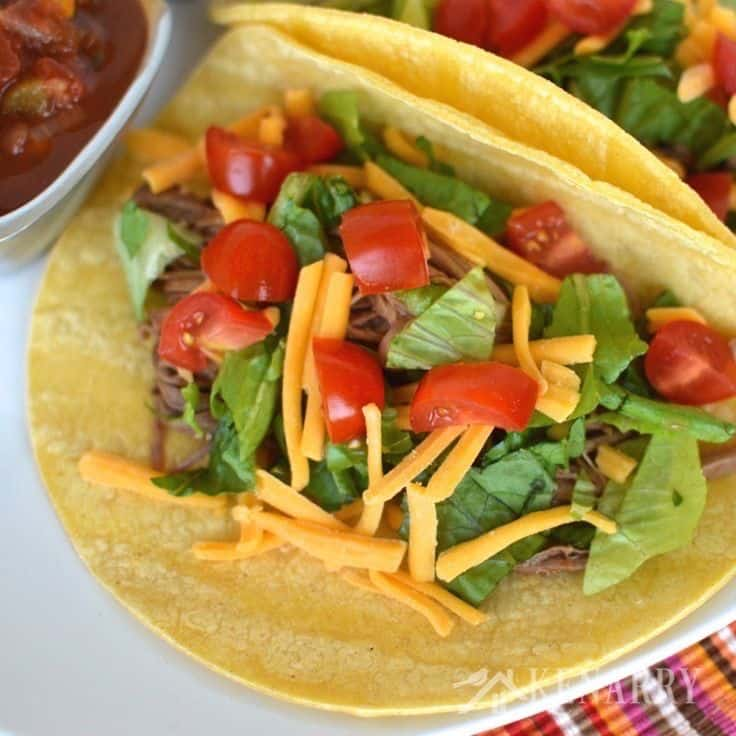 beef tacos on a plate topped with cheese, lettuce, and tomatoes