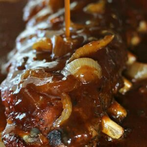A close up of ribs being poured with sauce