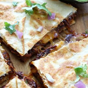 Juicy chicken cooks with a smoky bacon bbq sauce in your slow cooker, then pairs with gooey cheese to make these yummy quesadillas.
