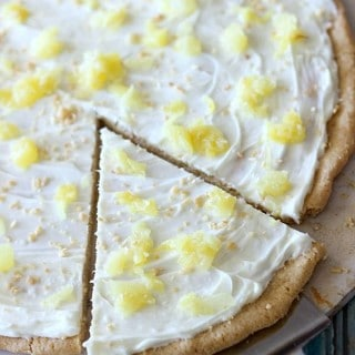 This Pina Colada Fruit Pizza is the perfect summer time treat! Made with a sugar cookie crust, a pineapple cream cheese frosting, and topped with juicy pineapple, you're going to want this all year round!