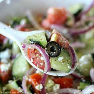 A close up of a spoon filled with tomatoes, cucumbers, red onion, black olives, and feta cheese