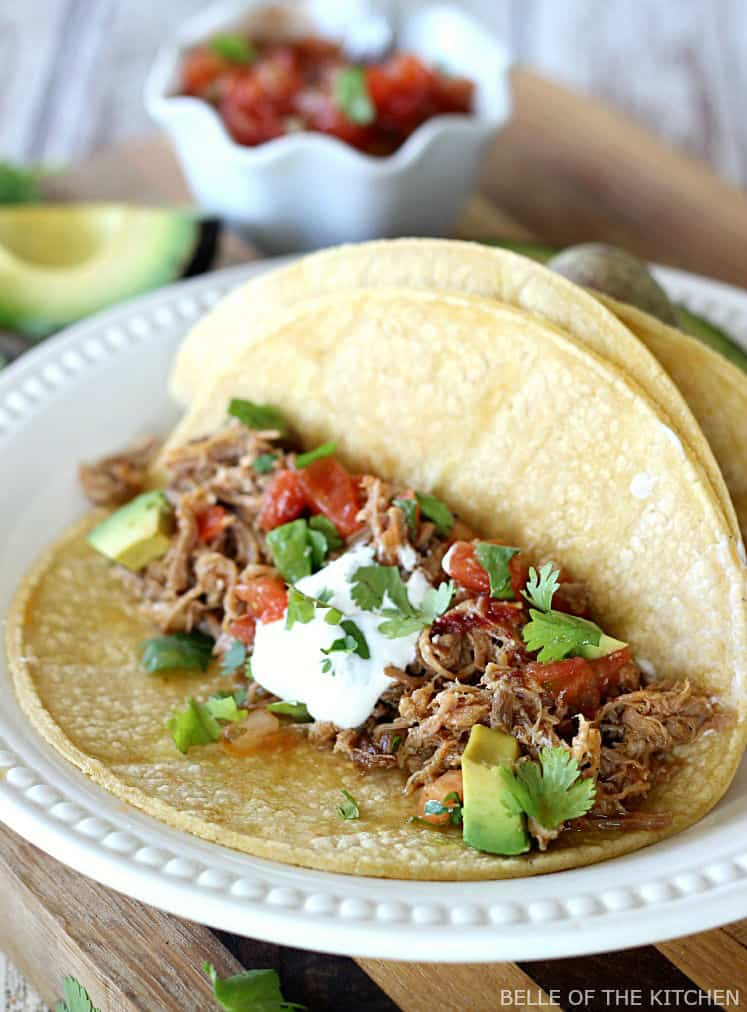 Slow Cooker Pork Carnitas - Flavorful, juicy pork that cooks all day in your crockpot. Serve over corn tortillas with with all of your favorite topping for a delicious, easy dinner.