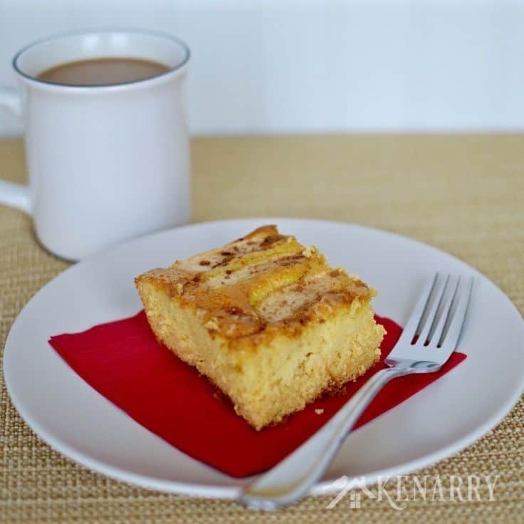 A piece of apple cake on a plate next to a cup of coffee
