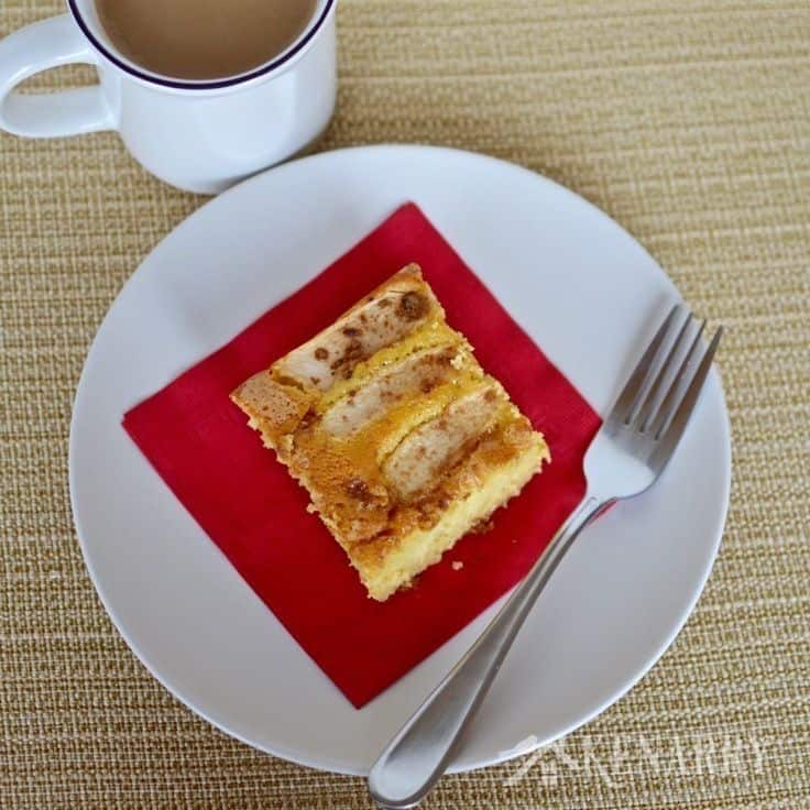 A piece of apple cake on a plate with a fork and red napkin