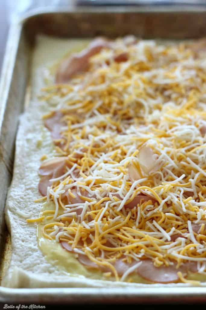 pizza dough on a sheet pan topped with ham and cheese