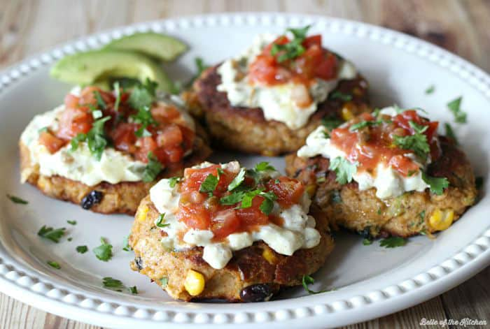 A plate full of tuna cakes topped with salsa, cilantro, and avocado