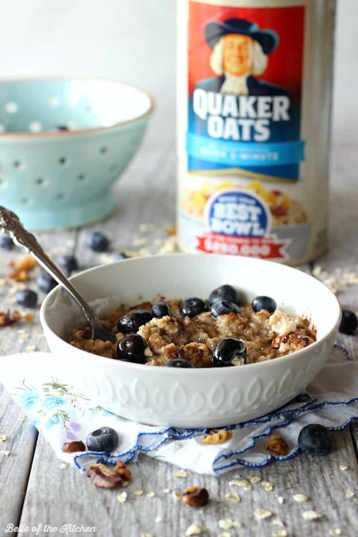 A bowl of oatmeal filled with blueberries with a can of oats in the background