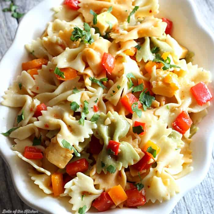A close up of a bowl of pasta salad with cheese and chopped peppers
