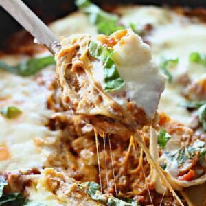 A close up lasagna with cheese being pulled out of a skillet