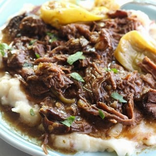 A plate of Mississippi pot roast on top of mashed potatoes
