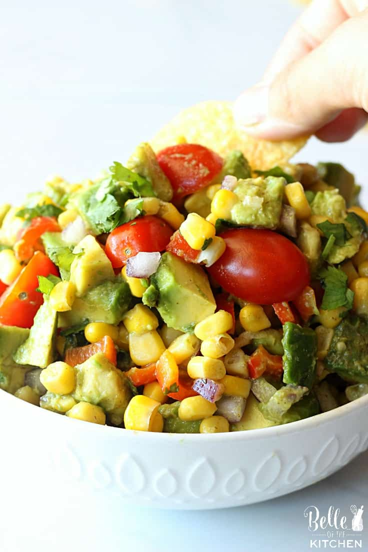 A dish filled with corn and avocado salsa with tomatoes and cilantro with a chip dipped in it