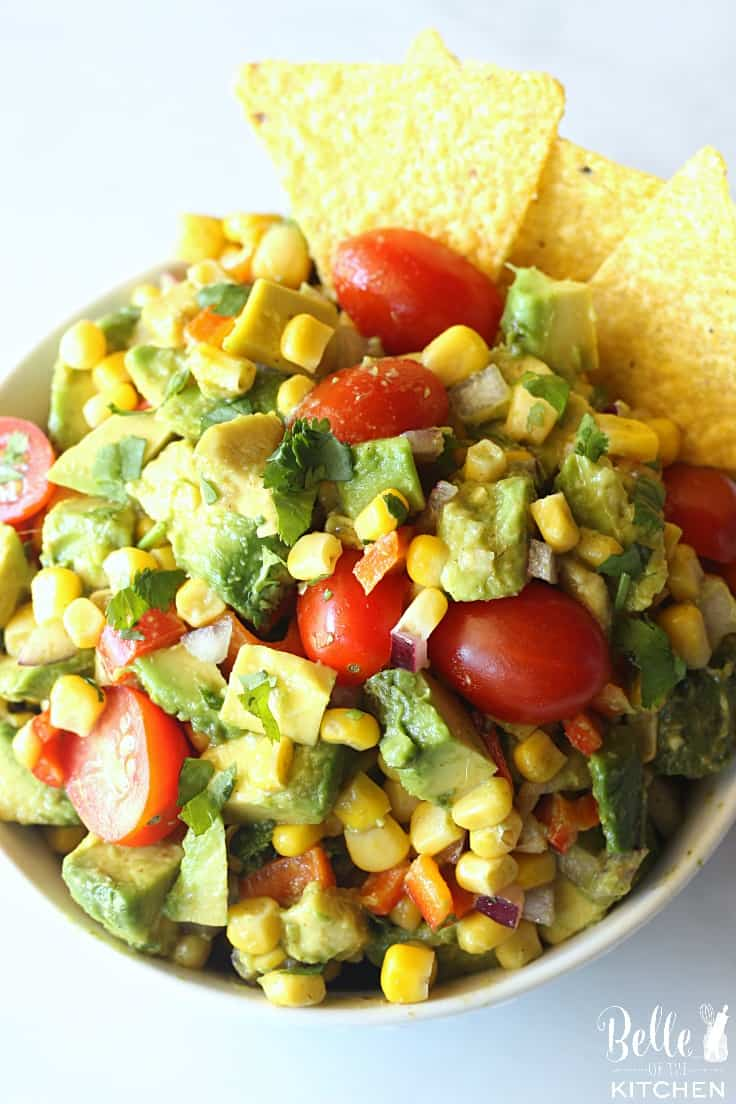A dish filled with corn and avocado salsa with tomatoes and cilantro