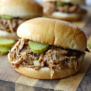 A close up of a sandwich with pulled chicken and pickles on a wooden cutting board