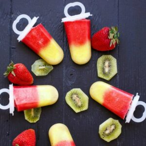 popsicles on a table surrounded by strawberries and sliced kiwi