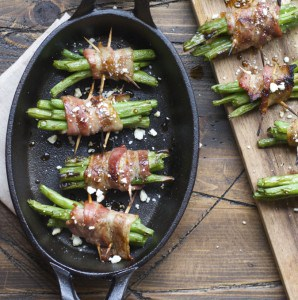 A close up of food on a wooden table, with Bacon and green beans bundles