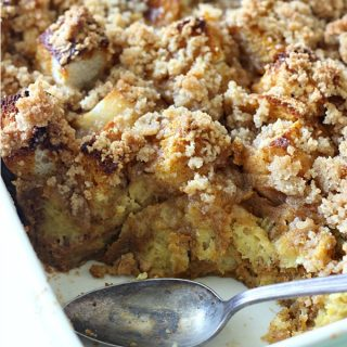 A dish filled with French toast casserole with a spoon